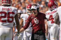 Oklahoma head coach Lincoln Riley congratulates running back Kennedy Brooks (26) and other players during the fourth quarter of an NCAA college football game against Texas at the Cotton Bowl, Saturday, Oct. 9, 2021, in Dallas. Oklahoma won 54-48. (AP Photo/Jeffrey McWhorter)