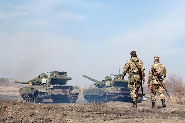 Ukrainian servicemen walk behind tanks as they take part in exercises near the eastern Ukrainian city of Lysychansk, in the Lugansk region on March 27, 2015 (AFP Photo/Petro Zadorozhnyy)