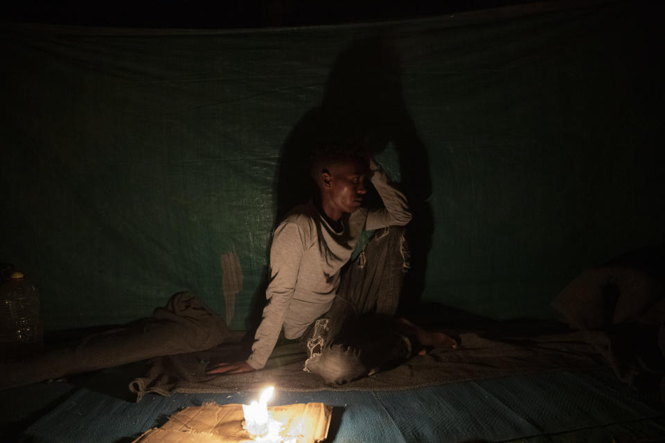 """Abedom, a 25-year-old day laborer and Tigrayan refugee, sits for a portrait inside his friends' shelter in Hamdayet, eastern Sudan, near the border with Ethiopia, on March 16, 2021. Abedom spent three months roaming in mountains and rural villages. """"It was normal to go a whole day without food. So many people were hungry. They loot everything, so if they take it all, how do I survive?"""" (AP Photo/Nariman El-Mofty)"""