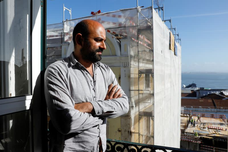 Hugo Fernandes poses on balcony with construction site seen nearby in Lisbon