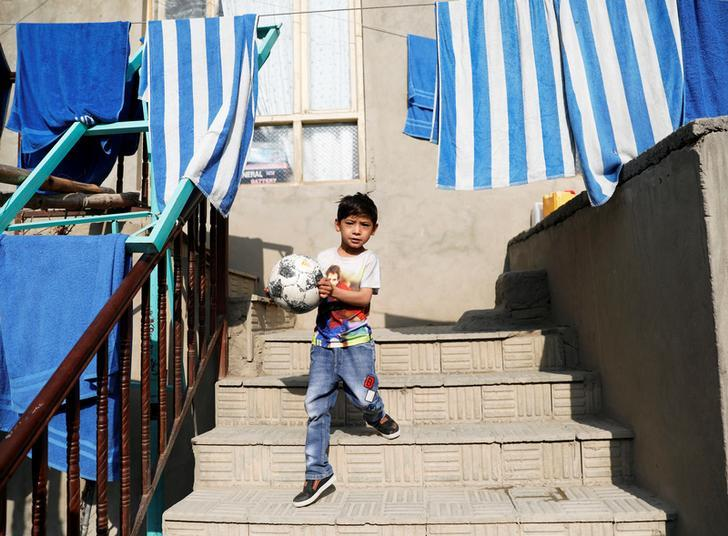Murtaza Ahmadi, 7, an Afghan Lionel Messi fan, walks in front of his house in Kabul, Afghanistan December 8, 2018. REUTERS/Mohammad Ismail