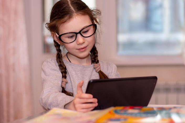 Distance learning online education.School girl with glasses does homework on tablet at home.Quarantine