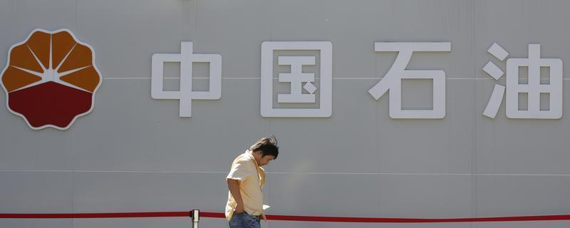 A man walks past a PetroChina company logo at its gas station in Beijing