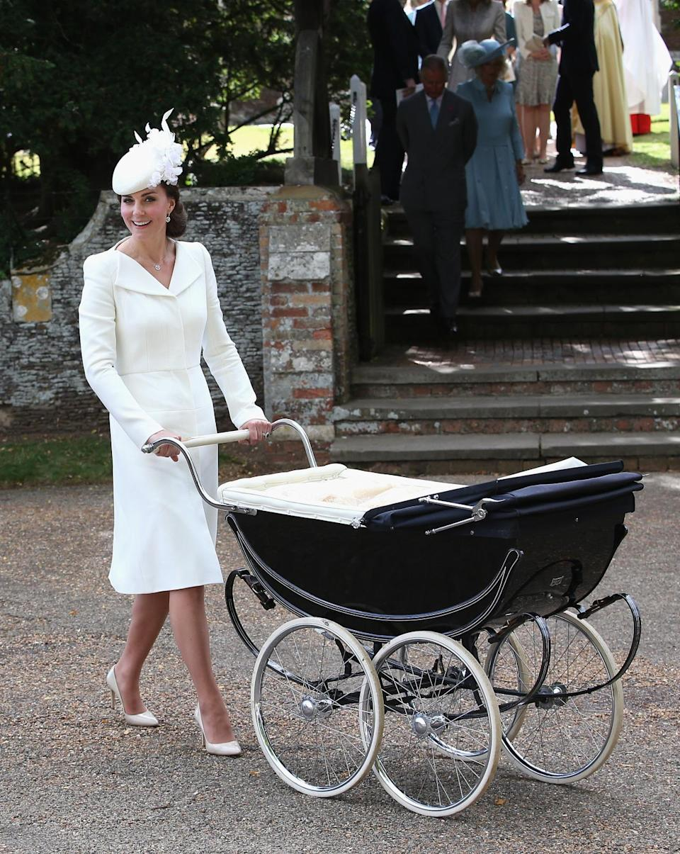 <p>The Duchess looked stunning in a bespoke white Alexander McQueen coat dress for Princess Charlotte's christening. Teaming the look with a matching floral Jane Taylor hat, Kate finished with nude Russell & Bromley heels.</p><p><i>[Photo: Getty]</i></p>
