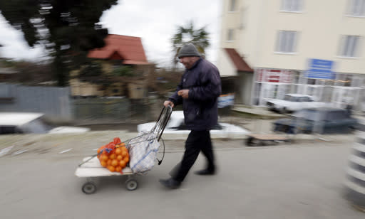 A man walks with his cart full of tangerines at the Abkhazian border Wednesday, Feb. 5, 2014, near Sochi, Russia. Abkhazia is a festering geopolitical sore, and the economic system still operating in these and many other parts of Russia is decidedly 19th century. As Russia opens its doors to a curious world with the Sochi Games, places like this border expose the vast contradictions still gripping the one-time superpower 21 years after the Soviet Union collapsed. (AP Photo/Morry Gash)