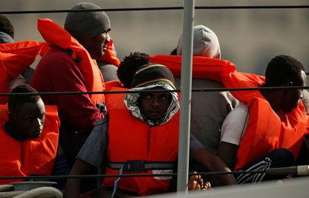 Migrants disembark from an Armed Forces of Malta patrol boat at its base in Marsamxett Harbour, Valleta