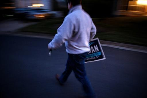 Mike Mullins, Juli Briskman's campaign manager, goes to set up a sign in a supporter's garden