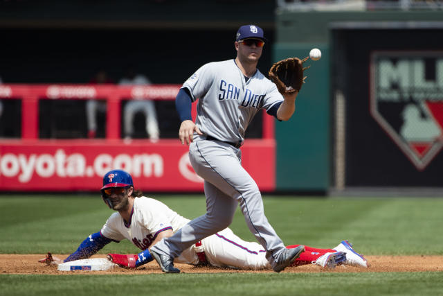 Philadelphia Phillies' Bryce Harper, bottom, advances to second base on a wild pitch ahead of the throw to San Diego Padres' Ty France during the second inning of a baseball game Sunday, Aug. 18, 2019, in Philadelphia. (AP Photo/Matt Rourke)