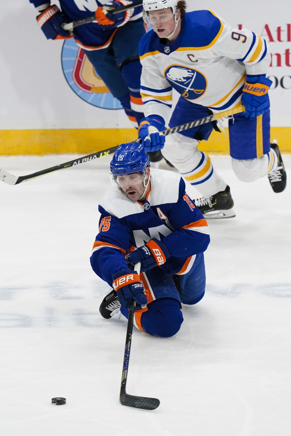 New York Islanders' Cal Clutterbuck (15) passes the puck away from Buffalo Sabres' Jack Eichel (9) during the second period of an NHL hockey game Thursday, March 4, 2021, in Uniondale, N.Y. (AP Photo/Frank Franklin II)