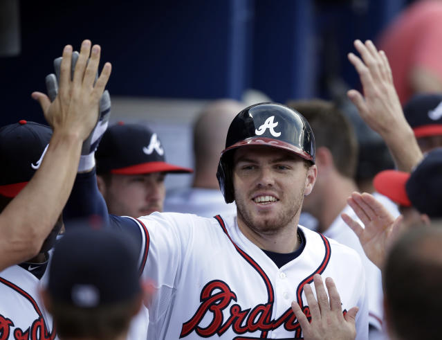 Atlanta Braves' Freddie Freeman celebrates in the dugout after hitting a solo home run in the first inning of a baseball game against the Colorado Rockies in Atlanta, Tuesday, July 30, 2013. (AP Photo/John Bazemore)