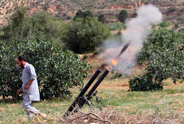 A fighter with Libya's UN-recognised Government of National Accord (GNA) fires rockets towards the city of Tarhuna, southwest of the capital Tripoli, held by the forces of the strongman Khalifa Haftar