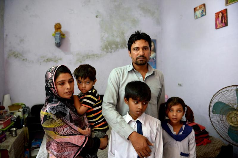 Bushra Parveen (L) and her husband Riaz Masih pose with their children at their home in Faisalabad, Pakistan, on May 9, 2014