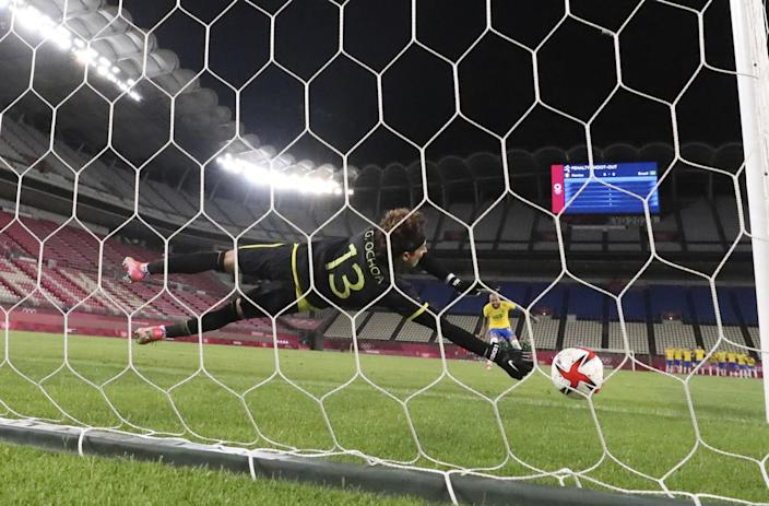 Mexico goalkeeper Guillermo Ochoa dives to his right but is unable to stop a penalty kick by Brazil's Dani Alves.