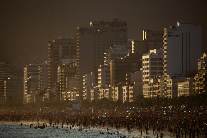 "FILE - In this Jan. 28, 2011 file photo, beachgoers are seen at dusk along the shore of Ipanema beach in Rio de Janeiro, Brazil. The bossa nova song, ""The Girl From Ipanema"" is turning 50, and to its legions of fans, the decades have only heightened its allure. The tune inspired by a young woman who passed the songwriters in a beach side bar on her way to the waters of Ipanema beach, carries within its chords and lyrics an image of a city that's light and easy, palm trees and blue sky, a sun-kissed life without care. (AP Photo/Felipe Dana, File)"