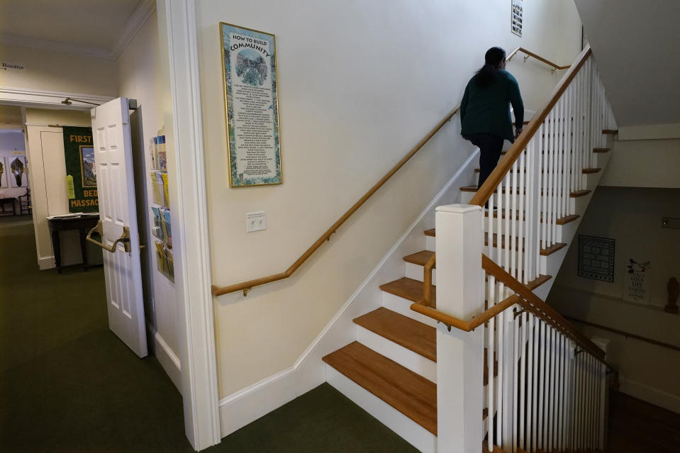 Maria Macario climbs the stairway to her temporary home at the First Parish church, Wednesday, Jan. 27, 2021, in Bedford, Mass. For three years, Macario has been too afraid to leave the confines of the church, which she moved in to avoid deportation, spending most of her time in a converted Sunday school classroom stocked with a hot plate, mini-fridge, TV and single bed. (AP Photo/Charles Krupa)