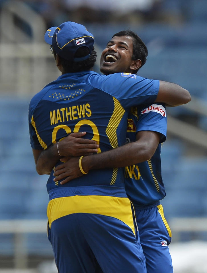 Sri Lankan cricketer Nuwan Kulasekara (R) embraces team captain  Angelo Mathews after dismissing Indian bastman Rohit Sharma during the third match of the Tri-Nation series between India and Sri Lanka at the Sabina Park stadium in Kingston on July 2, 2013. Sri Lanka have scored 348/1 at the end of their innings. AFP PHOTO/Jewel Samad
