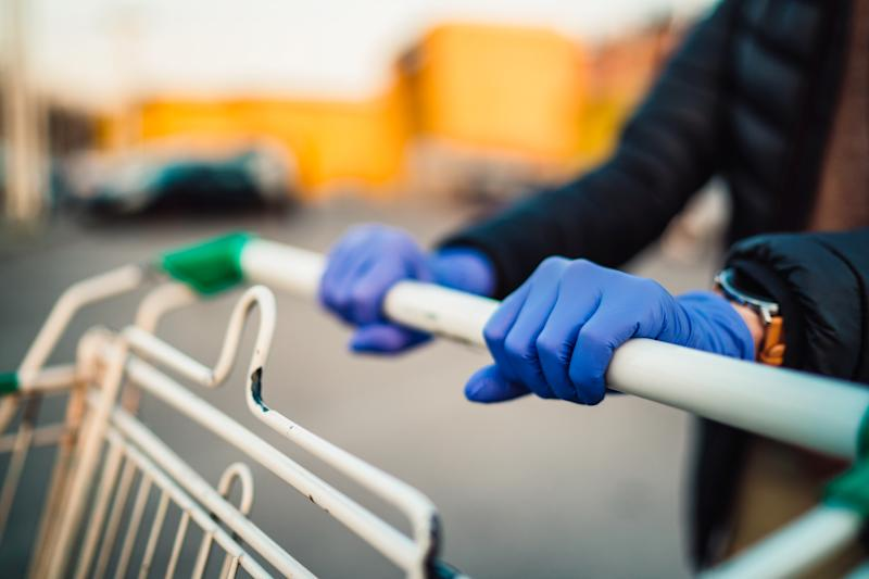 Close-up view of hands in rubber gloves pushing shopping carts in front of supermarket.