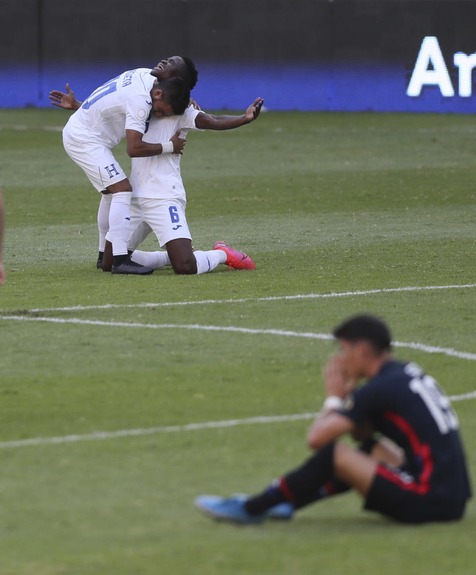Honduras' Carlos Argueta, top left, and Jonathan Nunez celebrates at the end of a Concacaf Men's Olympic qualifying championship semi-final soccer match in Guadalajara, Mexico, Sunday, March 28, 2021. Honduras defeated United States 2-1, qualifying for the upcoming Tokyo Olympics. (AP Photo/Fernando Llano)