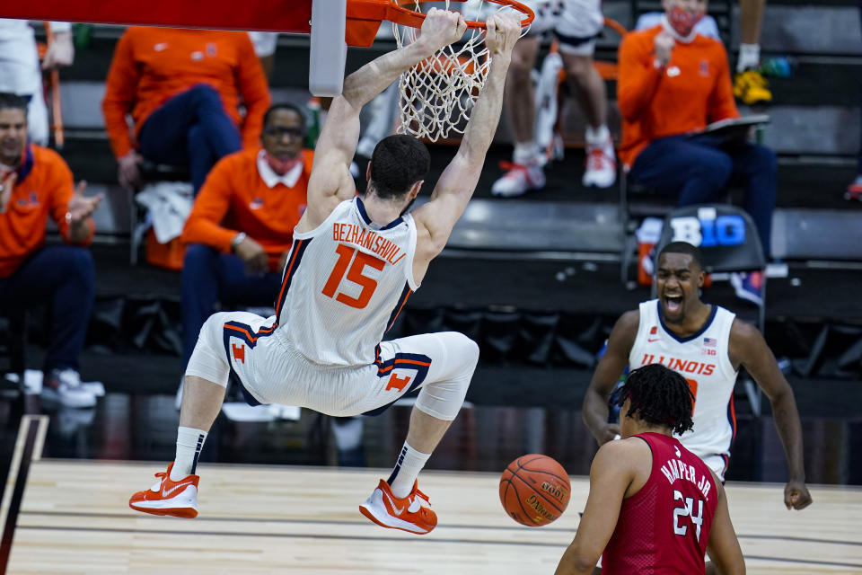 Illinois guard Da'Monte Williams, right rear, celebrates as Giorgi Bezhanishvili follows through on a dunk over Rutgers' Ron Harper Jr. during the second half of an NCAA college basketball game at the Big Ten Conference men's tournament in Indianapolis, Friday, March 12, 2021. (AP Photo/Michael Conroy)