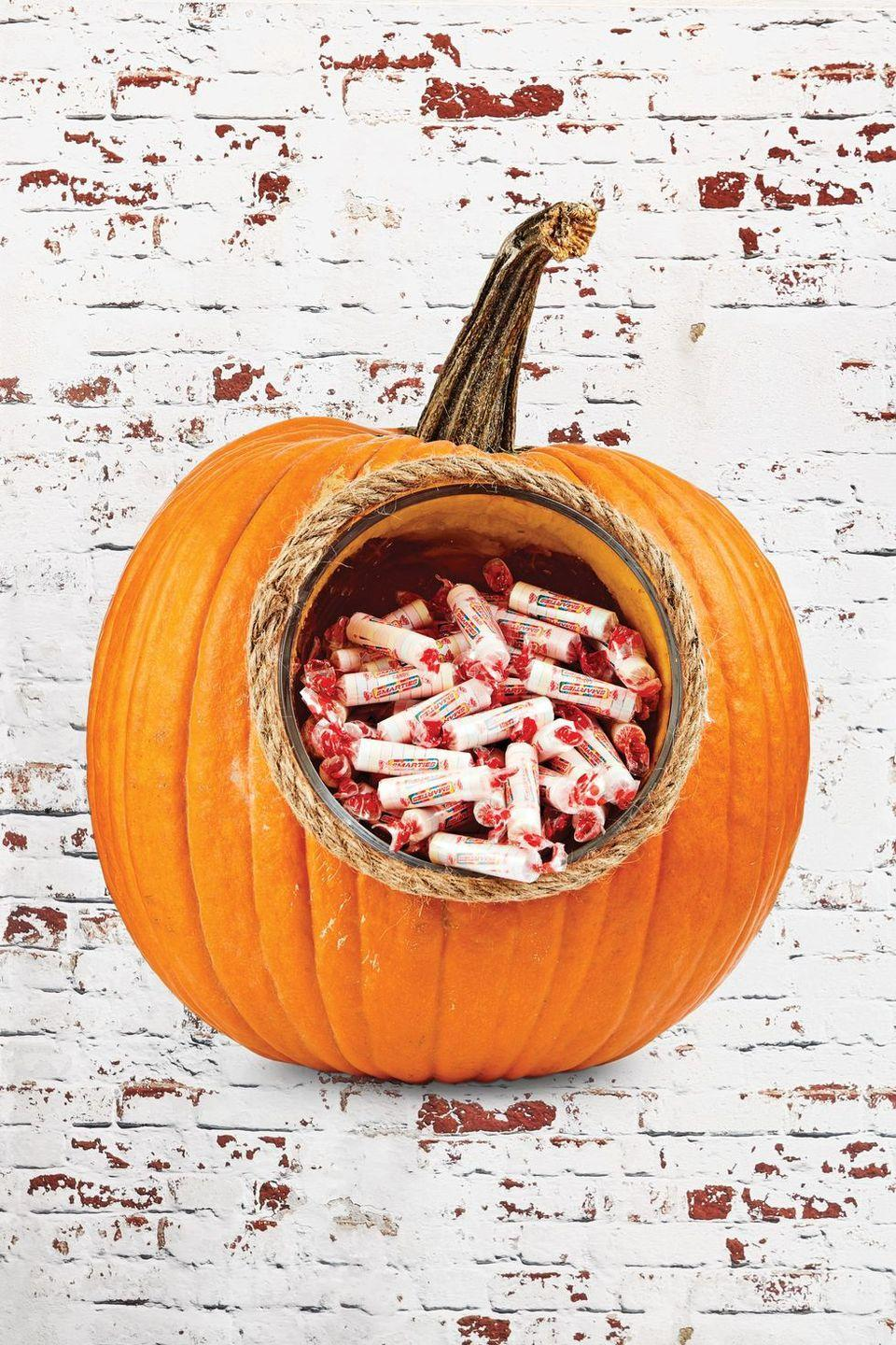 <p>This homemade beauty beats out any store-bought candy bowl. Just trace the bottom of a glass bowl or storage container to ensure that it'll fit inside. That way, you can safely store candy without covering it in the pumpkin's natural goop. </p>