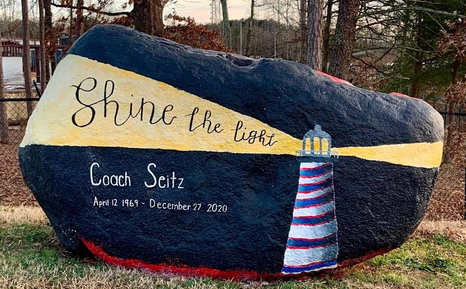 A painted rock on Lincoln Charter's campus in Denver, N.C., honors Jamie Seitz, who taught elementary school PE and coached high school basketball and golf for the school before dying of COVID-19. The red-and-blue colors of the lighthouse represent Seitz's favorite NFL team, the Buffalo Bills.