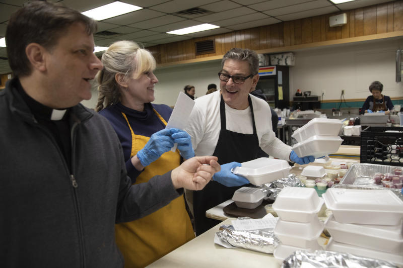 In this Feb. 28, 2020 photo, from left, Father Steve Kresak, parish priest at Holy Angels, jokes with Lisa Cotter and Joe Bilock as they prepare meals during the fish fry at Holy Angels parish in Pittsburgh. The church sells 2,000 pounds of fish each Friday during Lent. On March 12, Pittsburgh Bishop David Zubik suggested that people enjoy the fish fries with a take-out order rather than dining in due to virus concerns. (AP Photo/Rebecca Droke)