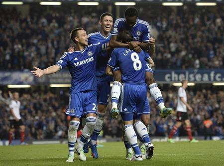 Chelsea's John Obi Mikel (top) celebrates with team mates after scoring against Fulham during their English Premier League soccer match at Stamford Bridge in London September 21, 2013. REUTERS/Dylan Martinez