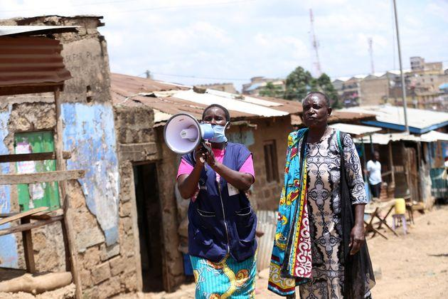 A health volunteer walks through slums in Nairoba, Kenya, informing residents about the coronavirus pandemic. More than 2.5 million people live n impoverished conditions in the city.