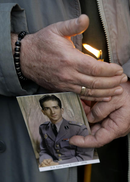 A royalist supporter holds up a candle and picture of Yugoslavia's last king — Peter II Karadjordjevic during a solemn ceremony in Belgrade, Serbia, Tuesday, Jan. 22, 2013. The former king fled the Nazi occupation of Yugoslavia at the start of World War II and never returned, as Communists took over at the end of the war. He died in exile and was buried at a Serbian Orthodox monastery in Libertyville, Illinois — the only European monarch buried on U.S. soil. (AP Photo/Darko Vojinovic)
