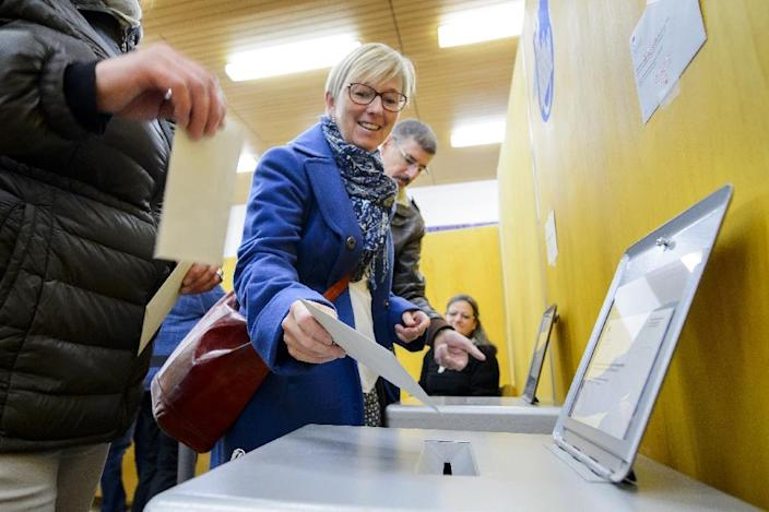 A woman casts her ballot at a polling station in Fribourg, western Switzerland, on October 18, 2015 (AFP Photo/Fabrice Coffrini)