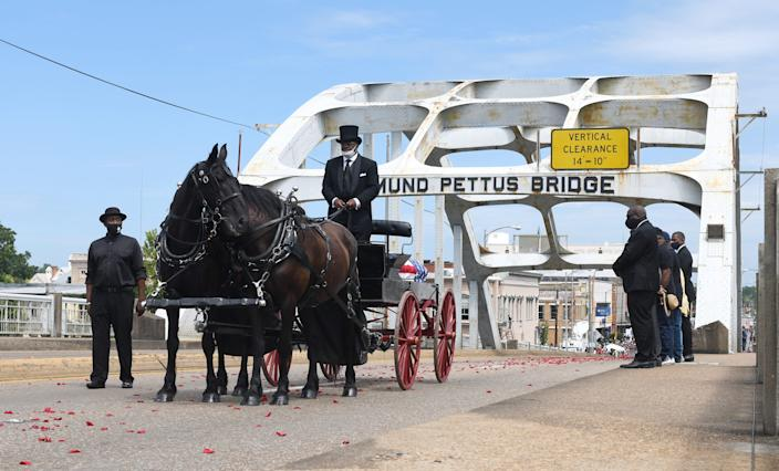 The body of civil rights icon and U.S. Rep. John Lewis is carried via horse-drawn carriage across the Edmund Pettus Bridge in Selma, Ala., on July 23, 2020.