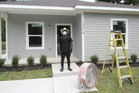 Houston resident Lloyd Nelms stands Tuesday, May 26, 2020, in front of his newly constructed home. Nelms' family home had to be torn down after it was flooded during Hurricane Harvey in 2017. Nelms said he was unable to get help from a city program created to fix homes damaged during Harvey and had to endure hazardous living conditions for more than two years. He turned to the Texas General Land Office to rebuild his home. The city program has finished rebuilding less than 70 homes since beginning in January 2019. (AP Photo/Juan Lozano)