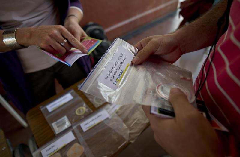 A midwife hands out condoms and gives sexual information to students at a university in Santiago, on April 11, 2012
