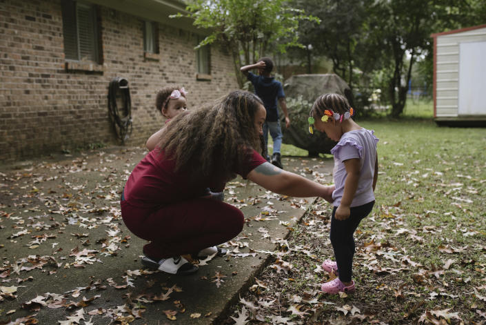 Brown dust off daughter Emery after she falls in the garden.  (Lucy Garrett for NBC News)