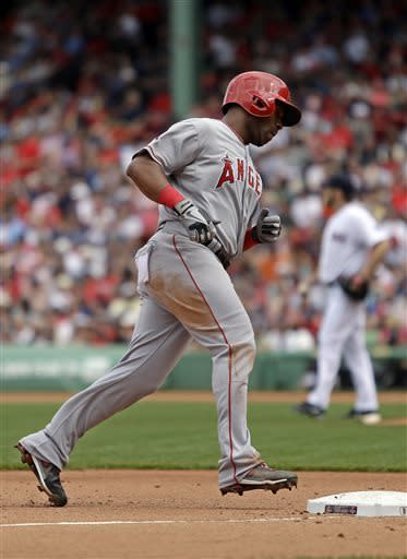 Los Angeles Angels' Alberto Callaspo, foreground, rounds third base after hitting a home run off Boston Red Sox starting pitcher Ryan Dempster, background, during the third inning of a baseball game on Sunday, June 9, 2013, at Fenway Park in Boston. (AP Photo/Mary Schwalm)
