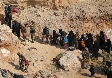 Islamic state fighters and their families walk as they surrendered in the village of Baghouz, Deir Al Zor province