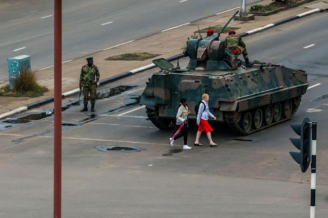 <p>Young women walk past an armoured personnel carrier that stations by an intersection as Zimbabwean soldiers regulate traffic in Harare on Nov. 15, 2017. (Photo: AFP/Getty Images) </p>