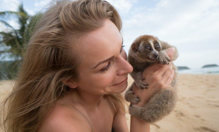 Woman on beach holds cute primate.