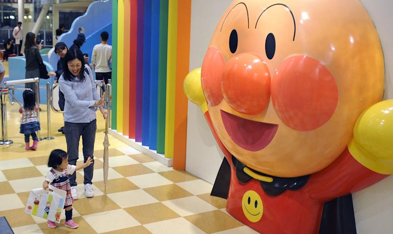 A girl reacts to a display of Anpanman at Yokohama Anpanman Children's Museum & Mall in Yokohama, southwest of Tokyo, Tuesday, Oct. 15, 2013. Takashi Yanase, creator of one of Japan's most beloved cartoon characters, Anpanman, died of heart failure at a Tokyo hospital early Sunday, Oct. 13, his studio said Tuesday. He had been treated for liver cancer since August. He was 94. (AP Photo/Kyodo News) JAPAN OUT, MANDATORY CREDIT