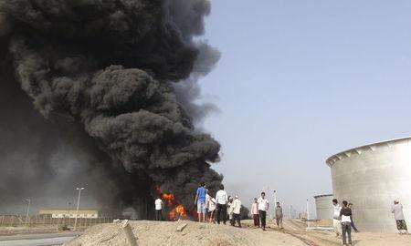 People gather at the site of a fire caused by missiles fired by Houthi fighters at storage tanks of the oil refinery in Yemen's southern port city of Aden