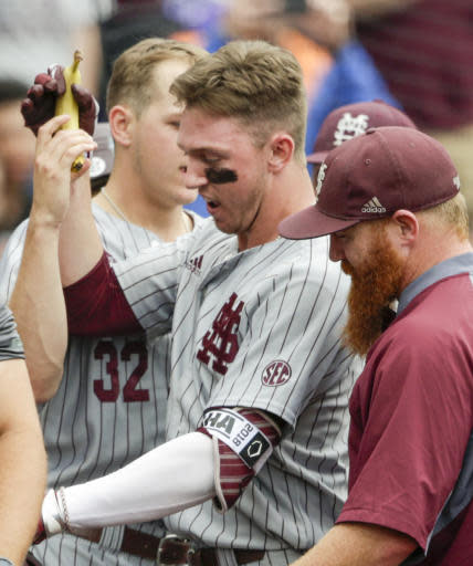 Mississippi State designated hitter Jordan Westburg, founder of the team's banana rally, is handed a banana at the dugout after hitting a grand slam in the second inning of an NCAA College World Series baseball game against North Carolina in Omaha, Neb., Tuesday, June 19, 2018. (AP Photo/Nati Harnik)
