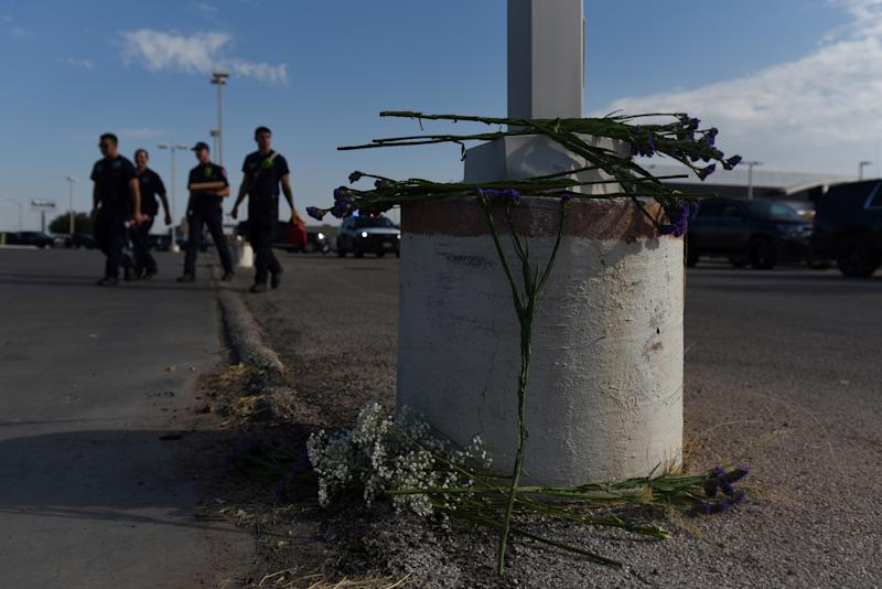 Flowers are seen as Texas state troopers and other emergency personnel monitor the scene at a local car dealership following a shooting in Odessa, Texas, U.S. September 1, 2019. REUTERS/Callaghan O'Hare