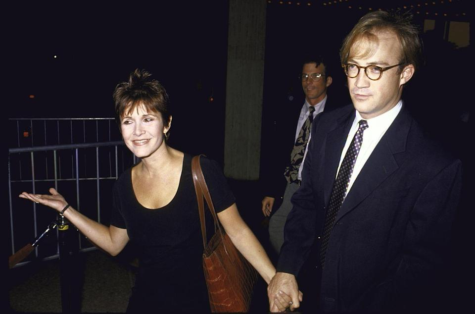 <p>In 1990, Carrie began a relationship with CAA talent agent, Bryan Lourd. Here, the couple attend a premiere in Hollywood together.</p>