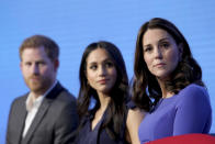 """FILE - In this Wednesday, Feb. 28, 2018 file photo, Britain's Kate, Duchess of Cambridge, right, with Prince Harry and his fiancee Meghan Markle attend the first annual Royal Foundation Forum in London. Britain and its royal family are absorbing the tremors from a sensational television interview with Prince Harry and Meghan. The couple said they encountered racist attitudes and a lack of support that drove Meghan to thoughts of suicide. The couple gave a deeply unflattering depiction of life inside the royal household, depicting a cold, uncaring institution that they had to flee to save their lives. Meghan told Oprah Winfrey that at one point """"I just didn't want to be alive anymore."""" Meghan, who is biracial, said that when she was pregnant with son Archie, there were """"concerns and conversations about how dark his skin might be when he's born."""". (Chris Jackson/Pool via AP, FIle)"""