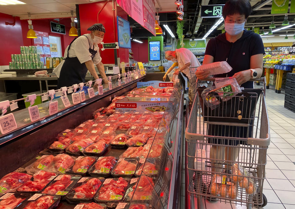 A resident wearing a face mask to curb the spread of the coronavirus browses meat products at a supermarket in Beijing, Monday, June 15, 2020. China's capital was bracing Monday for a resurgence of the coronavirus after more than 100 new cases were reported in recent days in a city that hadn't seen a case of local transmission in more than a month. (AP Photo/Ng Han Guan)