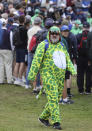 A gold fan dress as a dinosaur joins the crowd watch a practice round for the British Open Golf Championship at Royal St George's golf course Sandwich, England, Wednesday, July 14, 2021. The Open starts Thursday, July, 15. (AP Photo/Ian Walton)