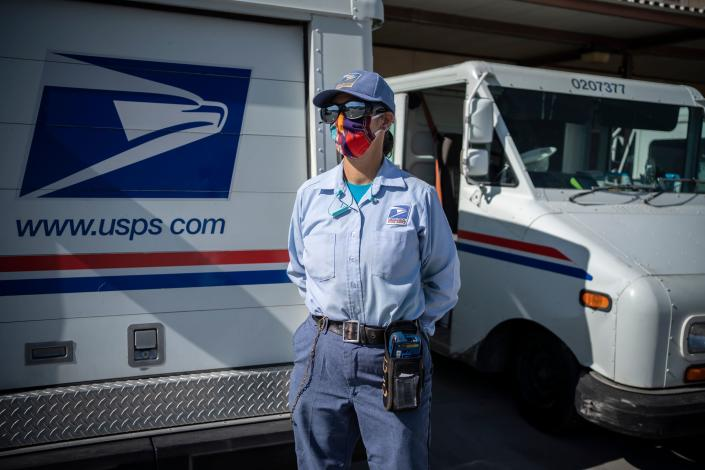 A United States Postal Service mail carrier poses in front of her truck before departing on her delivery route in El Paso, Texas. (PAUL RATJE/AFP via Getty Images)