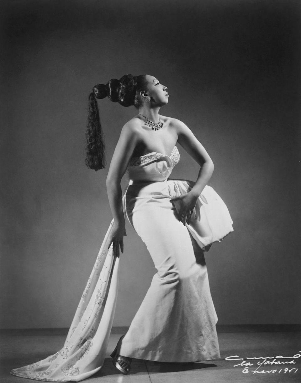 <p>A regal photograph of Baker, this image shows her in a beaded sweetheart evening gown, complete with an elegant train, fabulous jewelry, and a dramatic hairpiece. <br></p>