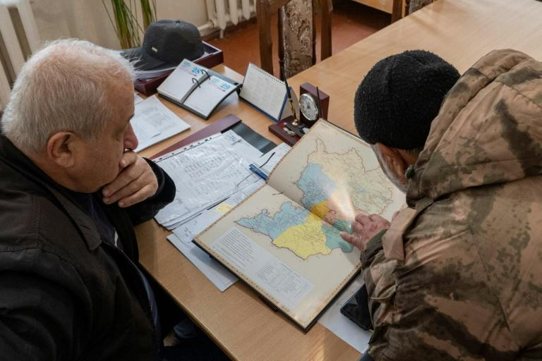 Armenian Vardges Harutyunyan (R) and Arvid Gulyan, Deputy head of Askeran district for agriculture look at the map of Nagorno-Karabakh and the Askeran district