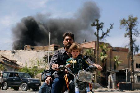 A man and a boy ride a motorbike at the city of Douma in Damascus